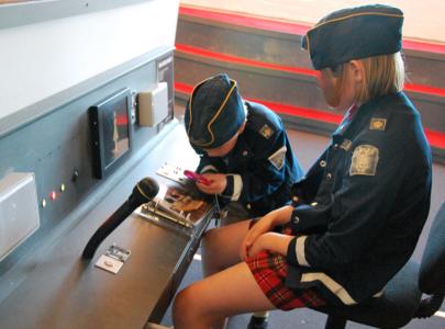 Sjuåringen och Tioåringen löser ett brott med hjälp av ledtrådar och förstoringsglas.