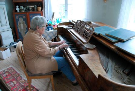 Vid en taffel mellan två stora golvur satt Fru Karin och spelade.