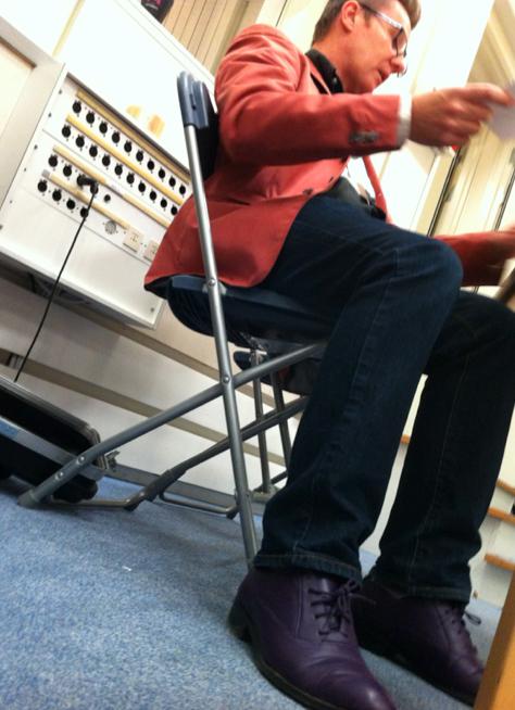 Han sitter där i sina lila Vi i femman-skor och förbereder sig på att ställa spontana frågor till barnen.