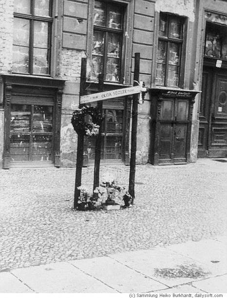 """Just här på Bernauer Straße låg huset i öst och trottaren i väst. På skylten står det """"Olga Segler"""", som var en ung flicka som hoppade från ett fönster i byggnaden och dog på trottoaren."""