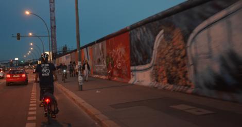 """Stora delar finns kvar, och när vi igår cyklade längs med den, kände vi nästan """"men vad händer bakom muren"""" … till några meter senare när muren öppnade sig och vi fick se vatten, människor, ölhak och konst."""