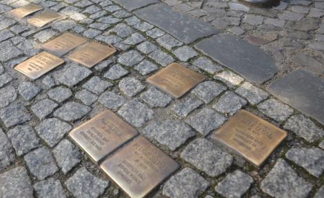 De här små minnesstenarna är verkligen inte roliga: de berättar om människorna som bodde i huset på just denna gata och när de mördades.