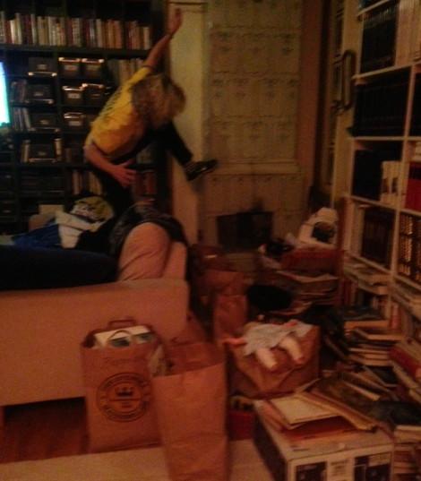 Det är inte helt lätt att sparka i kakelugnen eftersom hela vardagsrummet är belamrat med böcker som har rensats ut ur min mammas lägenhet.