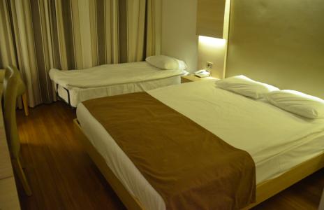 Mitt rum är stort och fint, men har en mystisk, lite skrynklig extrasäng i hörnet.